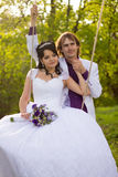 Bride and groom swinging on a swing Royalty Free Stock Photo