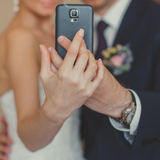 Bride and groom taking a selfie with a mobile phone. Stock Images