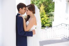 The bride and groom tenderly embrace and hide behind a white column, want to be alone, and escape from their wedding. stock photography