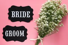 Bride and Groom text sign on pink background decorated with white flower bouquet, vintage style. wedding sign concept. Bride and Groom text sign on pink royalty free stock photo