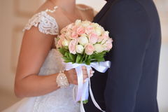 Bride and groom on their wedding day. Wedding couple hugging, the bride holding a bouquet of flowers in her hand stock image