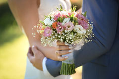 Bride and groom on their wedding day. Wedding couple hugging, the bride holding a bouquet of flowers in her hand stock images