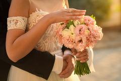 Bride and groom on their wedding day. Wedding couple hugging, the bride holding a bouquet of flowers in her hand royalty free stock photography