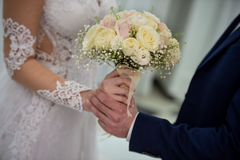 Bride and groom on their wedding day. Wedding couple hugging, the bride holding a bouquet of flowers in her hand royalty free stock image