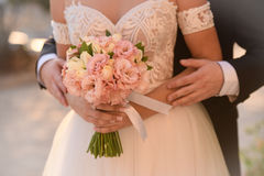 Bride and groom on their wedding day. Wedding couple hugging, the bride holding a bouquet of flowers in her hand stock photo