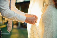 Bride and groom on their wedding day. Groom hold bride's dress in hands on their wedding day Royalty Free Stock Photos