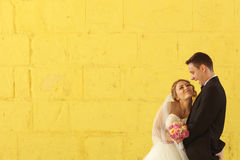 Bride and groom on their wedding day. On a yellow background Stock Photo
