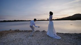 The bride and the groom throw stones into the water together. Sunset. Tropical ocean coast. Philippines. Shooting in. Motion stock footage