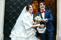 Bride and groom throw the sweets from a white basket Stock Images