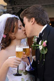 Bride and groom toasting. A newly married bride and groom kissing each other and toasting each other with glasses of wine Stock Images