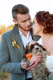 Bride and groom together with their little dog. Romantic autumn Stock Image