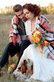 Bride and groom together with their little dog. Romantic autumn Royalty Free Stock Photos