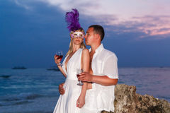 Bride and groom on a tropical beach drinking wine from glasses w Royalty Free Stock Images