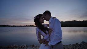 The bride and groom on a tropical beach near the ocean at sunset. Sensual hugs and kisses. Romance of love. The bride and groom on a tropical beach near the stock footage