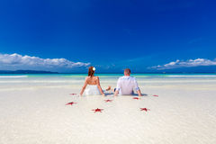Bride and Groom on tropical beach shore with red starfis Royalty Free Stock Photo