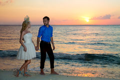 Bride and groom on a tropical beach with the sunset in the backg Stock Images