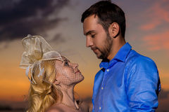 Bride and groom on a tropical beach with the sunset in the backg Royalty Free Stock Photography