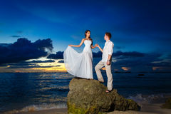 Bride and groom on a tropical beach with the sunset in the backg Royalty Free Stock Image