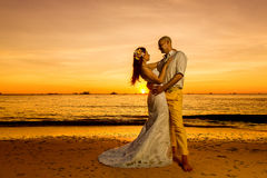 Bride and groom on a tropical beach with the sunset in the backg Royalty Free Stock Photo