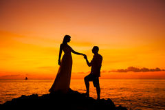 Bride and groom on a tropical beach with the sunset in the backg. Round silhouette photo Stock Photos