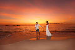 Bride and groom on a tropical beach with the sunset in the backg. Bride and groom walking on a tropical beach with the sunset in the background Stock Image