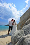 Bride and groom on tropical beach under umbrella Royalty Free Stock Images
