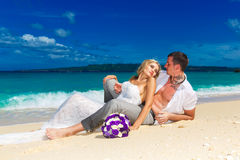 Bride and groom on a tropical beach. wedding bouquet in the fore. Ground Royalty Free Stock Images