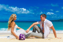 Bride and groom on a tropical beach. wedding bouquet in the fore. Ground Royalty Free Stock Photography