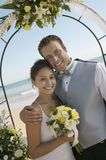 Bride and Groom under archway on beach royalty free stock image