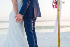 The bride and groom under archway on beach. Calm and romantic white sandy beach for honeymoon destination and love background Royalty Free Stock Photography