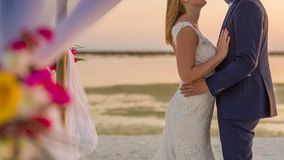 The bride and groom under archway on beach. Calm and romantic white sandy beach for honeymoon destination and love background Royalty Free Stock Photos