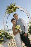 Bride and Groom under archway on beach (portrait) Stock Image