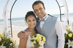 Bride and Groom under archway on beach (portrait) Stock Photo