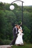Bride and groom under lantern Stock Photos