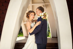 Bride and groom under stone arch Stock Photo
