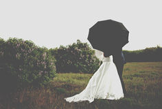Bride and groom under umbrella Royalty Free Stock Images