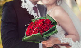 Bride And Groom Under Veil Holding wedding Bouquet In Hand. Stock Photo