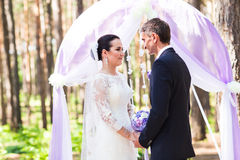 Bride and Groom Under wedding arch Stock Photo