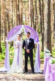 Bride and Groom Under wedding arch. Stock Photos