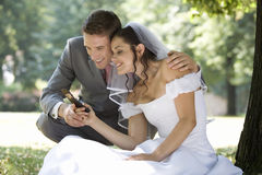 A bride and groom using a mobile phone Royalty Free Stock Photos