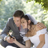 A bride and groom using a mobile phone Stock Photography
