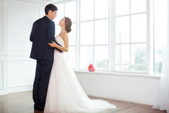 Bride and groom in very bright room Royalty Free Stock Photography