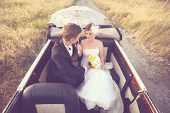 Bride and groom in a vintage car Stock Photo