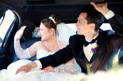 Bride and Groom waiving to the guests. Bride and groom in a limo waving to the guests, while departing Royalty Free Stock Photo
