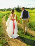 The bride and groom walk along the path. The groom holds the bride`s hand. love road. The bride and groom walk along the path. The bridegroom takes the bride`s Stock Images