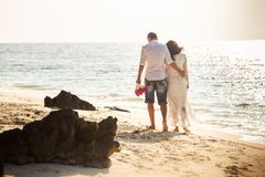 Bride and groom walk along sea Stock Images