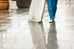 Bride and groom walk along wet pavement street. Bride and groom walk on wet city square. White dress and blue suit, rain. Reflection in puddles Stock Image