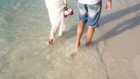 Bride and groom walk barefoot in shallow water with waves stock video