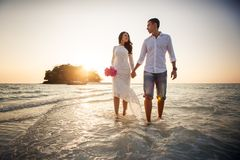 Bride and groom walk barefoot at spit Royalty Free Stock Photo