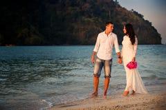 Bride and groom walk  at  beach at dawn Stock Image